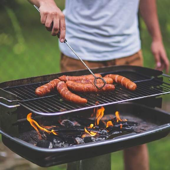 Person grilling sausages about charcoal bbq