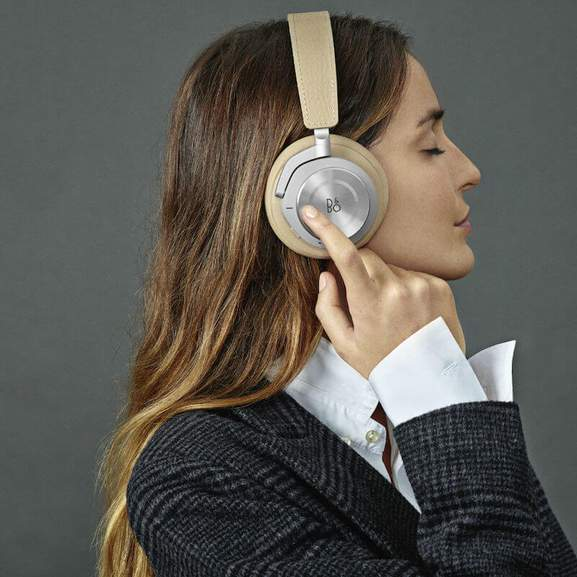 BeoPlay H9i wireless headphones on head with hand pressing button