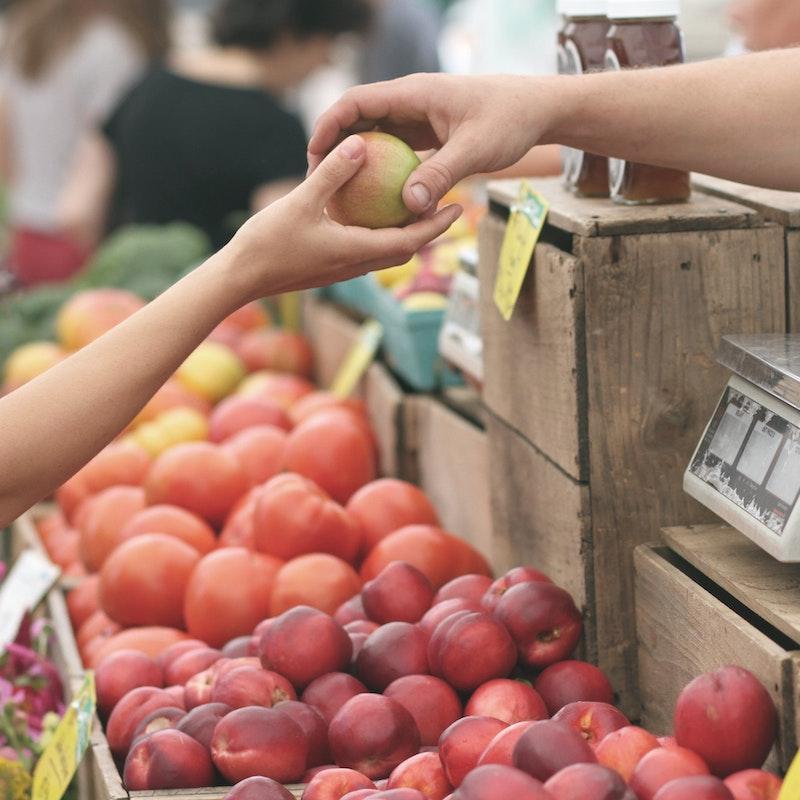 fruit exchanging hands in supermarket