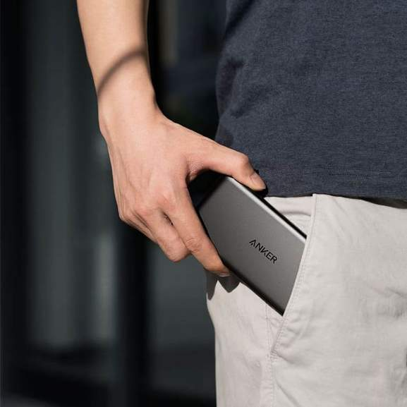 Anker PowerCore being put in pocket of beige shorts
