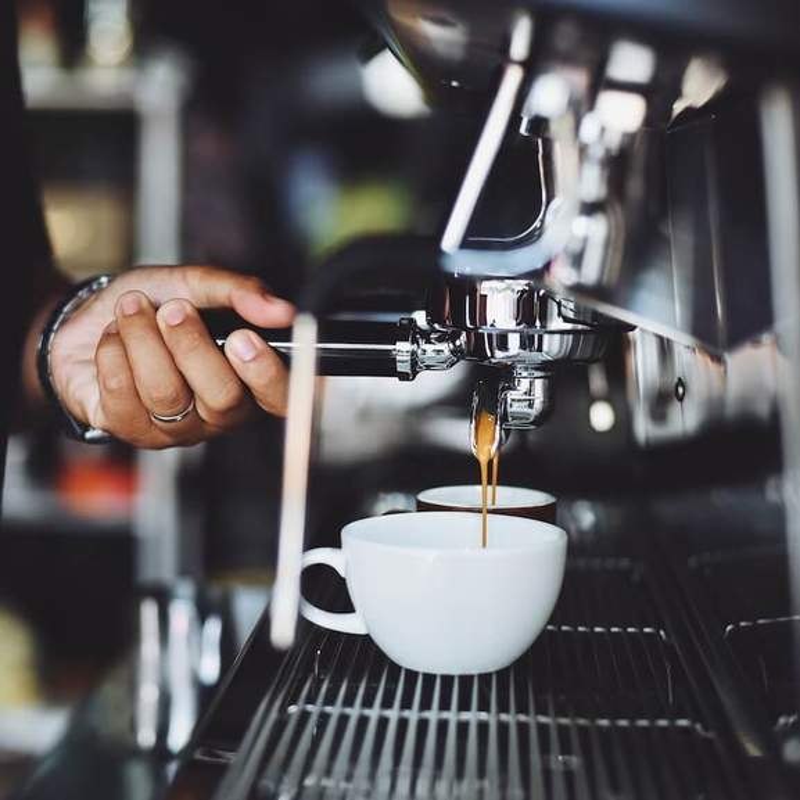 espresso machine making coffee into two mugs