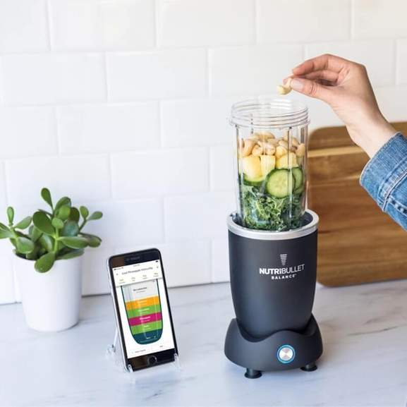 Person using nutribullet to create smoothie