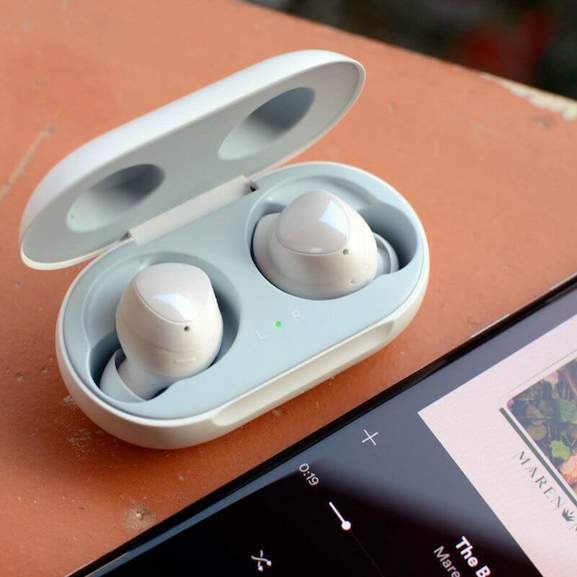 White Samsung Buds in ear next to phone