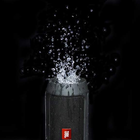 Black JBL portable speaker splashing with water