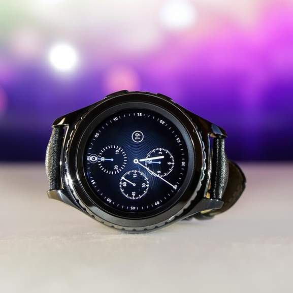 Samsung Gear S3 in front of purple and pink background