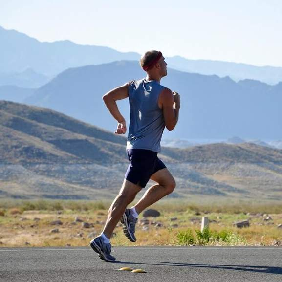Man running in running vest in front of mountains