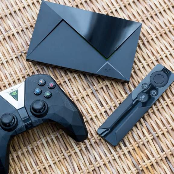 Nvidia shield game controller next to normal controller and nvidia shield console