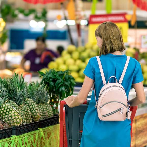 person at supermarket by pineapples