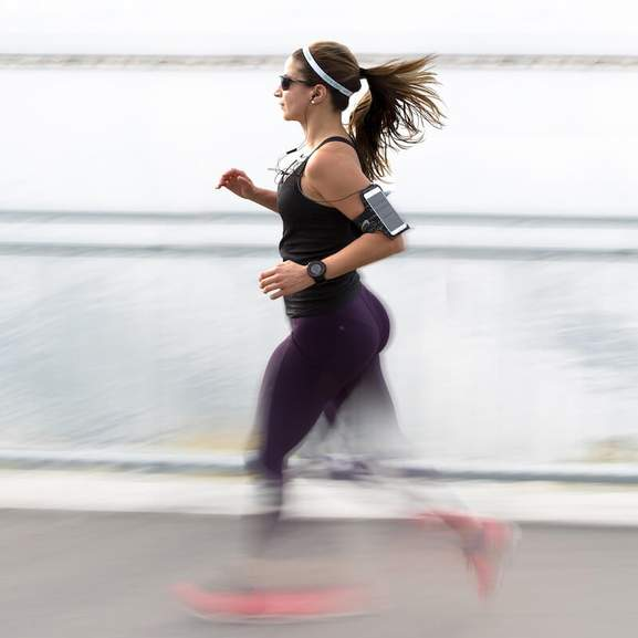Woman running with running phone holder on arm and running headphones with motion blur on legs