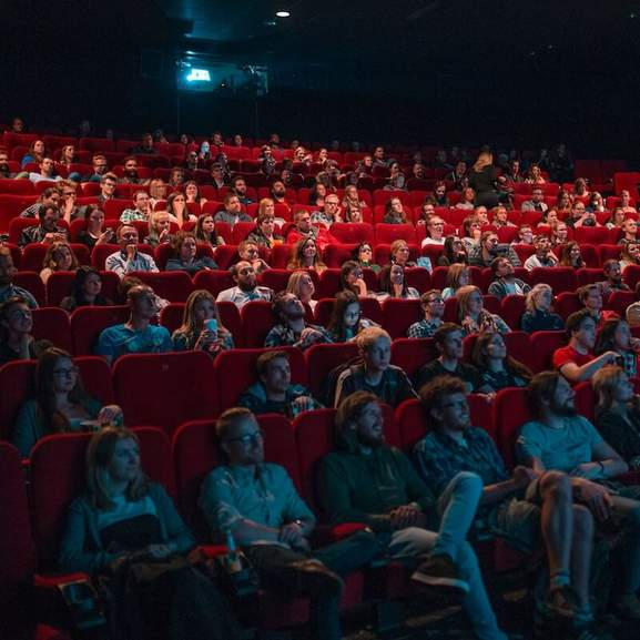 Cinema Theatre with people on red seats