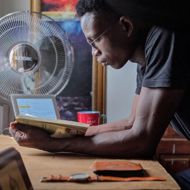 Man reading book in front of desk fan