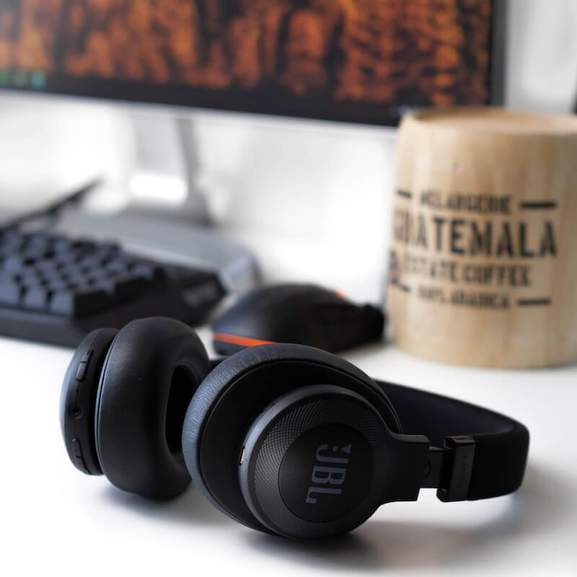 Black JBL wireless headphones on desk in front of computer